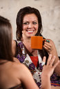 Smiling Woman Drinking Coffee with Friend Stock Photos