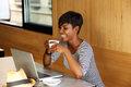 Smiling woman drinking coffee and looking at laptop Royalty Free Stock Photo