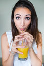 Smiling woman drinking orange juice at home portrait of Stock Photos