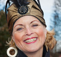 Smiling woman with earrings and a golden hat.