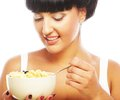 Smiling woman eating muesli portrait of young or cornflakes Stock Photography