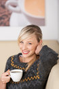 Smiling woman enjoying coffee in a cafe sitting relaxing with cup of espresso her hand Stock Image