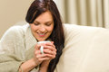 Smiling woman enjoying hot tea sitting on couch Stock Image