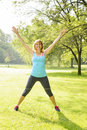 Smiling woman exercising outside female fitness instructor doing jumping jacks in green park Royalty Free Stock Image