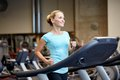 Smiling woman exercising on treadmill in gym Royalty Free Stock Photo