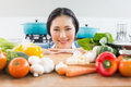 Smiling woman in front of vegetables in kitchen portrait a young the at home Stock Photography