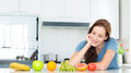Smiling woman with fruits on counter in kitchen young the at home Stock Images