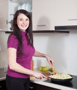 Smiling woman frying eggplant in griddle at home kitchen Royalty Free Stock Photos