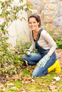 Smiling woman gardening yard fall hobby housework kneeling dry leaves Stock Photo