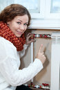 Smiling woman gesturing when turning thermostat on heating radiator central Stock Photo