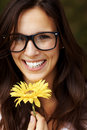 Smiling woman girl in glasses with a yellow flower Royalty Free Stock Image