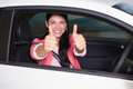 Smiling woman giving thumbs up in her car at new showroom Stock Image
