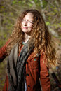 Smiling woman with glasses and blonde curly hair on sunny forest background Stock Photos
