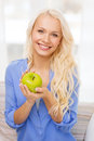 Smiling woman with green apple at home diet health and concept yoing Stock Photo