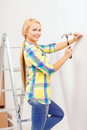 Smiling woman hammering nail in wall reapir building and home renovation concept Stock Image