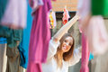 Smiling woman hanging clothes after laundry to dry on line Royalty Free Stock Image