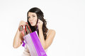 Smiling woman happy with her purchase attractive young giving the viewer a sneak peek as she lifts it out of a purple shopping bag Royalty Free Stock Photography