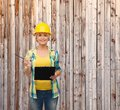 Smiling woman in helmet with clipboard repair construction and maintenance concept Royalty Free Stock Photo