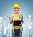 Smiling woman in helmet with clipboard repair construction and maintenance concept Stock Photography
