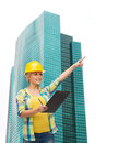 Smiling woman in helmet with clipboard repair construction and maintenance concept pointing finger Stock Image