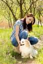 Smiling woman with her cute dog casual young crouched down beside little long haired toy breed on a rural pathway Royalty Free Stock Image