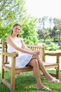 Smiling woman with her legs crossed  sitting on a park bench Stock Images