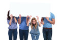 Smiling woman holding banner with her friends hiding casual people behind a blank board one women looks to the camera and one men Royalty Free Stock Image