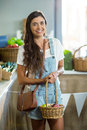 Smiling woman holding a basket of apples in the grocery store Royalty Free Stock Photo