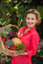 Smiling woman holding basket full of vegetables outdoors. Healthy lifestyle.