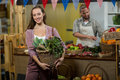 Smiling woman holding basket of green leafy vegetables in the grocery store Royalty Free Stock Photo
