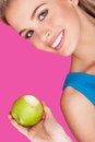 Smiling woman holding a bitten apple beautiful with wide toothy smile fresh green to prove her healthy diet over pink Royalty Free Stock Image