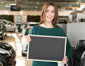 Smiling woman holding blackboard inside car dealership cardboard in front of cars Stock Photos