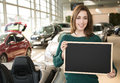Smiling woman holding blackboard inside car dealership cardboard in front of cars Stock Photo