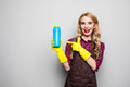 Smiling woman holding bottle of chemistry for cleaning house and pointed on. Royalty Free Stock Photo