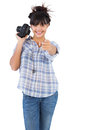 Smiling woman holding camera and pointing her finger on white background Royalty Free Stock Photos