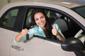 Smiling woman holding car key while giving thumbs up Royalty Free Stock Photo