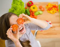 Smiling woman holding cherry tomatos in front of face young kitchen Stock Image