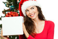 Smiling woman holding christmas gift a beautiful wearing a santa hat and a big white present and looking at copy space isolated on Stock Image
