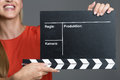 Smiling woman holding a clapperboard during film production to give the sound to commence recording of the audio during each new Royalty Free Stock Image