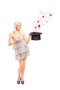 Smiling woman holding a hat and hearts coming out Royalty Free Stock Photos