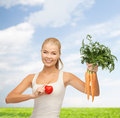 Smiling woman holding heart symbol and carrots Royalty Free Stock Photos