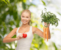 Smiling woman holding heart symbol and carrots health diet food concept young Stock Image