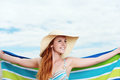 Smiling woman holding out towel young in strawhat and bikini top against the sky Stock Photos