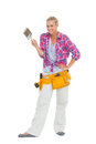 Smiling woman holding paint brush wearing a tool belt on white background Royalty Free Stock Photography