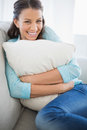 Smiling woman holding pillow sitting on couch in bright living room Stock Photo