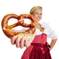 Smiling woman holding a pretzel in dirndl into the camera Royalty Free Stock Photography