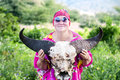 Smiling woman holding a skull of a buffalo