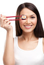 Smiling woman holding sushi roll with a chopsticks Royalty Free Stock Images