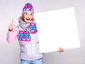 Smiling woman holds the banner with thumbs up sign in winter outerwear Royalty Free Stock Photo