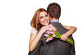 Smiling woman hugging her husband women men and holding a bouquet of tulips the concept of valentine s day Royalty Free Stock Photo